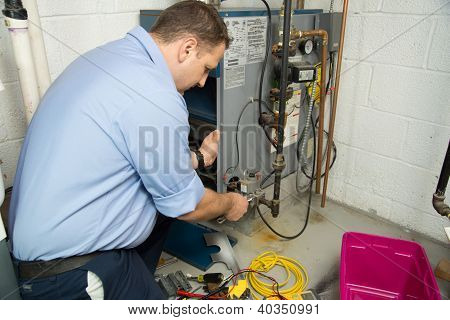 Plumber fixing gas furnace using electric and plumbing tools. Plumber in uniform working on gas furnace. Electric and plumbing tools, electric wire. poster