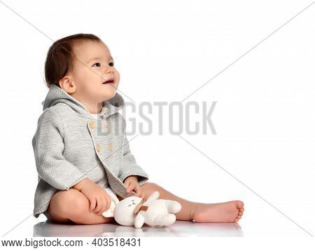 Baby And Toy Bunny Isolated. Barefoot Infant Child In Knitted Wear Sitting On White Floor Studio Bac