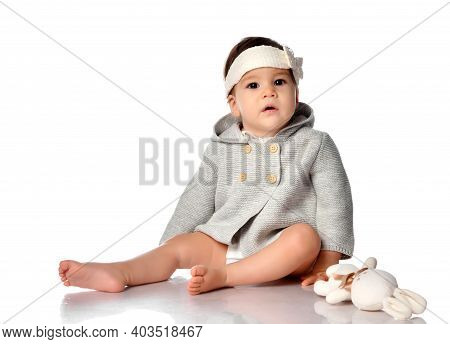 Barefoot Infant Child In A Knitted Dress And Headband, Looks At The Camera While Sitting On White Ba