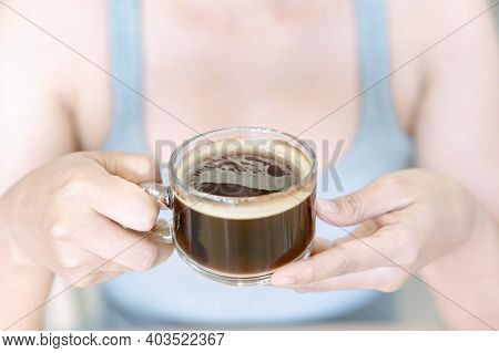 Closeup Woman Hand Holding Glass Of Hot Americano Coffee, Selective Focus, Vintage Tone