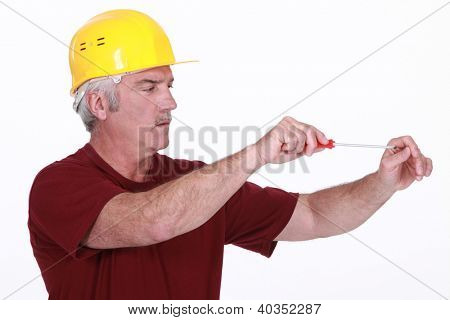 Middle-aged handyman using screw-driver