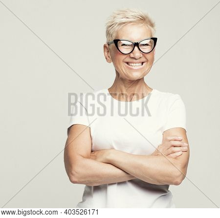 Aged people, lifestyle and maturity concept: blonde fifty year old European female with stylish pixie haircut and eyeglasses smiling at camera and posing isolated over grey background.