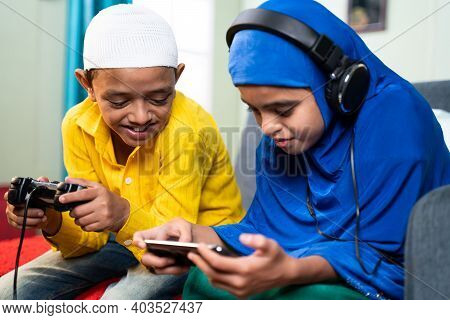 Concept Of Kids Busy With Modern Day Technology Lifestyle And Distraction - Two Muslim Siblings, Bro