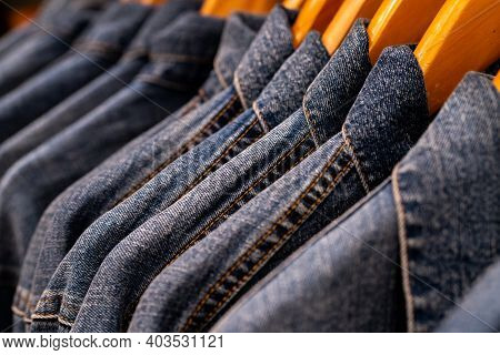 Selective Focus On Jacket Jeans Hanging On Rack In Clothes Shop. Denim Jeans With Jeans Pattern. Tex