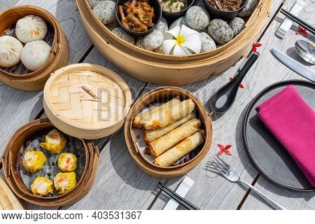 Dimsum Hagao In Chinese Bamboo Basket. Gyoza On A Wooden Table In A Restaurant. Assorted Asian Food