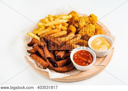 The beer plate with spicy chicken wings, calamari rings, fries onion rings, cheese balls, breaded, ketchup and mustard sauce