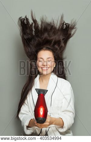 Smiling Woman Holding Red Hair Dryer On White Background