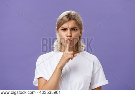 Close-up Shot Of Serious Strict Good-looking Caucasian Female With Blond Hair Shushing At Camera Dis
