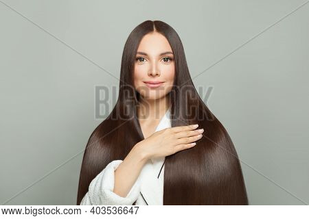Pretty Woman With Long Healthy Straight Hair On White Background. Haircare Concept