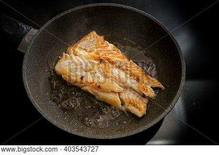 Cod Fish Fillet Sautéed In Butter In A Frying Pan On The Stove, Selected Focus, Narrow Depth Of Fiel