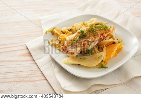 Cod Fish Fillet On Sauteed Fennel Vegetable With Orange Slices And Leek Served On A White Plate And
