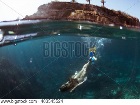Freediver Girl With White Fins Glides Near Rock Cave With Sun Rays. Freediving Underwater In Sea