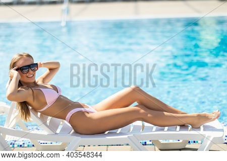Portrait Of Woman With Cocktail Glass Chilling In The Tropical Sun Near Swimming Pool On A Deck Chai