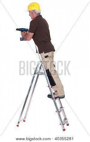 Tradesman standing on a stepladder and using a power tool poster