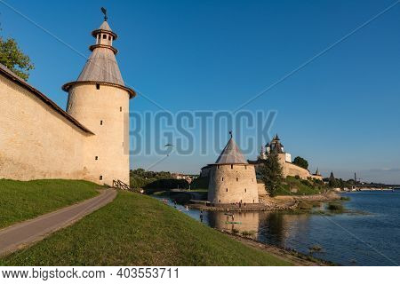 Pskov Kremlin View From River Pskova Creek. Towers, Wall And Trinity Cathedral On Background. Russia