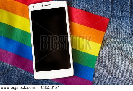 White Smartphone On Rainbow Lgbt Flag And Denim Background, Lesbian, Gay And Bisexual Tolerance And