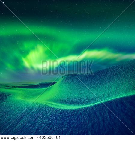 Aurora borealis over fantastic winter landscape in snowy mountains. Dramatic wintry scene with frozen snowy hills and Northern lights. Courtesy of NASA. Photo collage