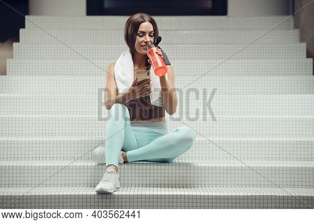 Fitness Woman With Cell Phone At Workout In The Gym