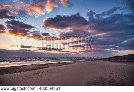A Stormy Beach During Sunset. The Sky Is Orange/blue And Filled With Dark Clouds. The Water Of The S