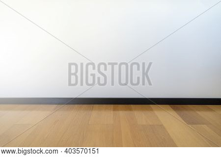 Empty Room With Wooden Floating Laminate Flooring. House Interior, Wide Bedroom Or Living Room Space