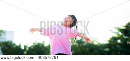 Happy Little Asian Cute Girl Spread Both Arms And Tilted Neck. Sweet Smile Child Holding Hands Up. L