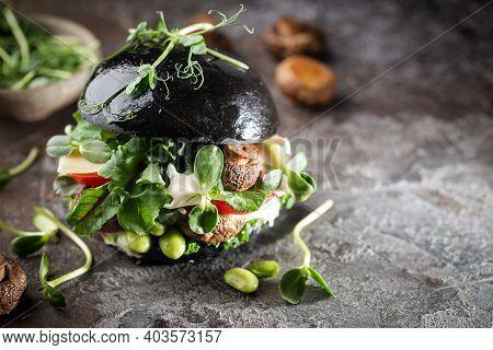 Veggie Mushroom, Green Salad And Vegetable Black Burgers. On Gray Stone Background Copyspace.