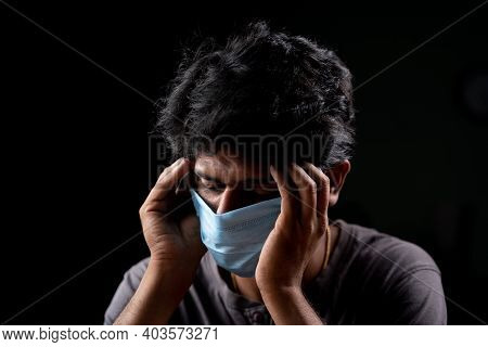 Young Man With Medical Mask Holding His Head Due To Headache After Receiving Vaccine Shots - Concept
