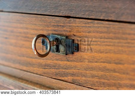 Secret, Mystery Concept. Close Up View Of A Retro Key On An Old Fashioned Keyhole, Wooden Drawer Bac