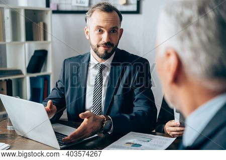 Businessman Pointing At Laptop Near Papers And Investor On Blurred Foreground In Office