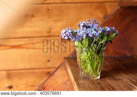 Blue Wildflowers In A Glass Cup On A Wooden Background. Forget Me Nots.