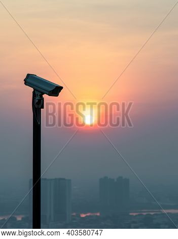 Modern Surveillance Camera On Cityscape And Skyscraper Background With Sun Shing Bright Before The S