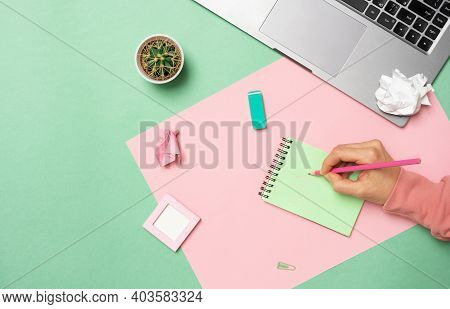 Office Desk Top View. Workplace With Girl Hands, Laptop, Cactus, Notepad, Pink With Green Background