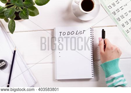 Top View Mockup Of Womans Hand With Notepad On White Wooden Background Calendar, Cup Of Coffee And F