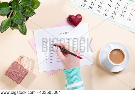 Woman Hand Writes A List In A Blank Notebook, A Wooden Heart, A Gift Box And A Flower On A Light Tab
