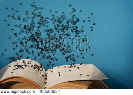 Letters Of The Alphabet In Levitation In The Air Over The Open Book Pages
