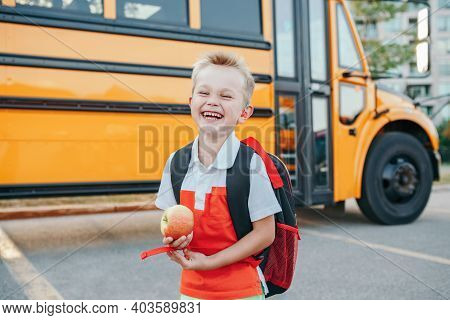 Happy Laughing Smiling Caucasian Boy Student By Yellow Bus On First September Day. Hard Of Hearing C