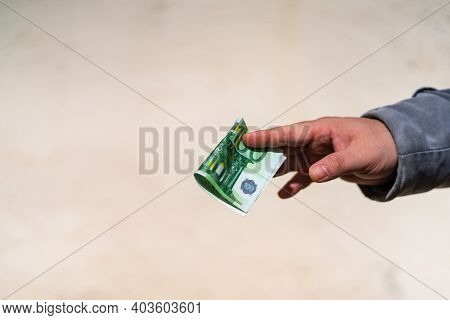 Man Hand Giving Money Like A Bribe Or Tips. Holding Euro Banknotes On A Blurred Background, Euro Cur
