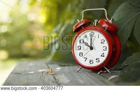 Red Classic Alarm Clock In The Garden. Save Time, Daylight Saving Concept, Web Banner With Copy Spac
