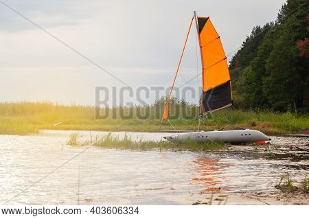 Inflatable Sailing Catamaran With Raised Sails On The River Near The Shore. Summer Sports Concept, F