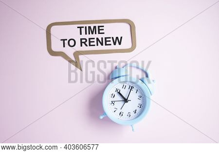 Text Time To Renew Isolated On Pink Background With Alarm Clock.