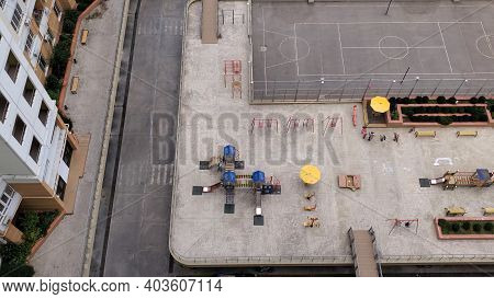 Top View Of Kids Playground Near Basketball Court Between Residential Condo Buildings Of Big City. A