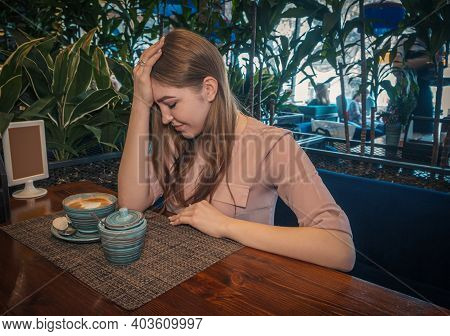 Heartbroken Young Lady Is Sitting In Cafe And Thinking Regretfully. Depressive Lady Drinks Coffe In