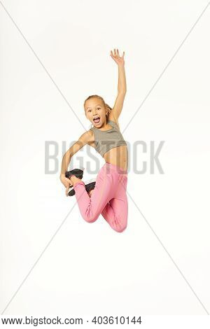 Cheerful Adorable Girl Jumping And Screaming With Joy