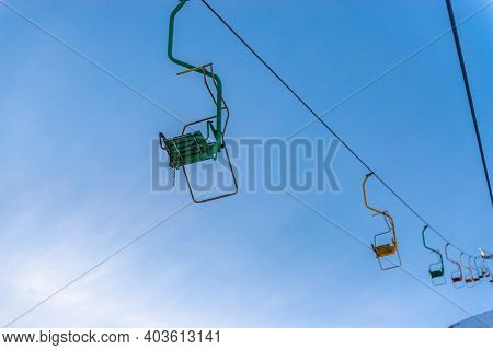 The Old Chair Lift On Mount Cheget. Multicolored Chairlifts Going Up.