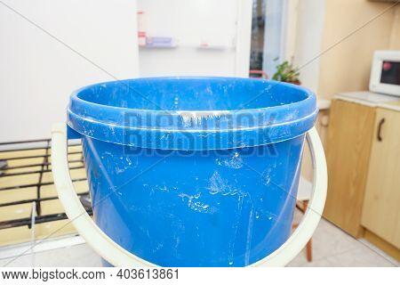 Blue Dirty Plastic Pail With Paint And Cement Stains While Construction And Renovation Of Kitchen