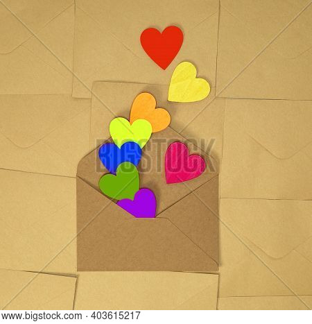 Brown Craft Paper Envelope With Various Rainbow Colorful Hearts On Plain Brown Background Texture To