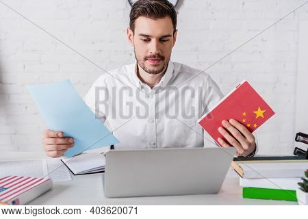 Smiling Interpreter Holding Chinese Dictionary And Document Near Laptop In Translation Agency