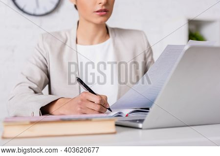 Cropped View Of Translator Writing In Notebook While Holding Document Near Laptop, Blurred Foregroun