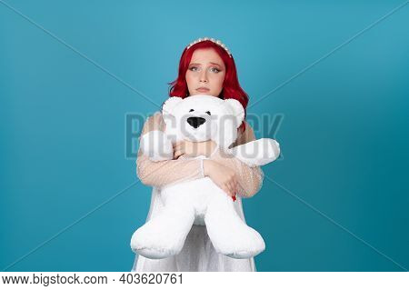 Sad, Hurt, Disappointed, A Woman In A White Dress With Red Hair Gently Hugs A White Teddy Bear Isola
