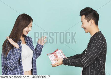 Young Man Giving Present To Beautiful Woman